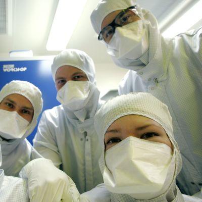 Tutkijoita suoja-asuissa puhdastilalaboratoriossa