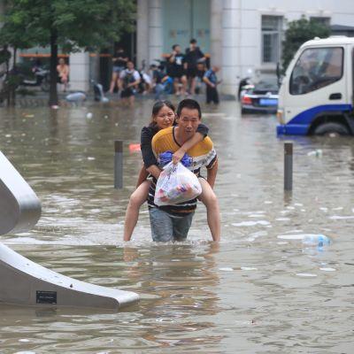 En man bär en kvinna på ryggen genom den översvämmade staden Zhengzhou.