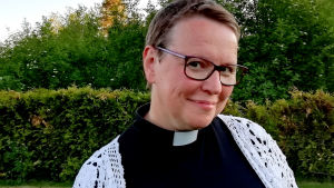 En korthårig kvinna i närbild ler mot kameran. Kvinnan har prästskjorta på sig och en vit virkad tröja. I bakgrunden gröna träd och en häck.