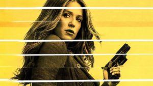 Nainen pyssyn kanssa, katsoo kameraan, keltaisella, raidoitetulla taustalla.