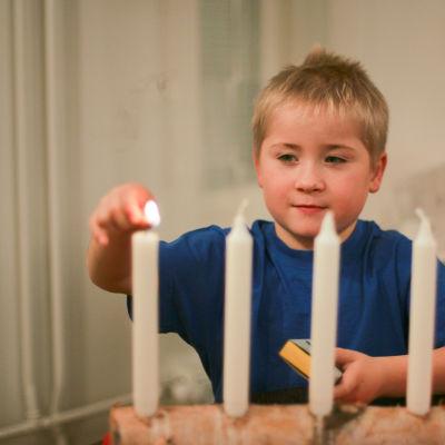 Pojke tänder det första ljuset i adventstaken.