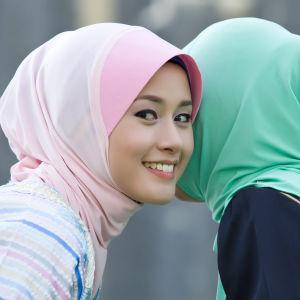 Två muslimska tjejer talar med varandra.