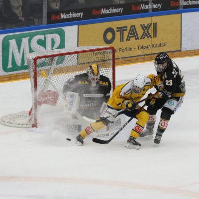 Kärpät- och Jukuritspelare kämpar om pucken framför Kärpäts mål.