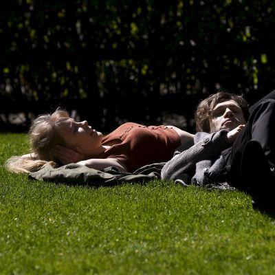 Två personer ligger på rygg i gräset.