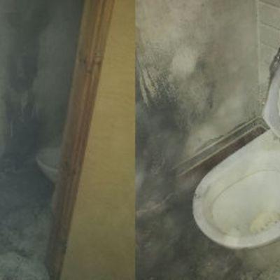 Mustunut seinä ja wc-pönttö, jonka kansi sulanut osittain.