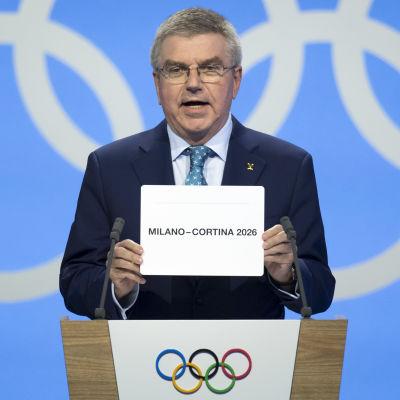 Thomas Bach håller upp en lapp där med värden för vinter-OS 2026 namn.