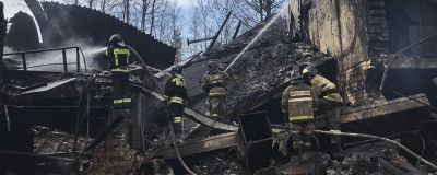 Brandmän släcker elden i nedbrända fabriken.