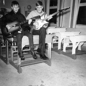 Kaksi nuorta miestä istuu luokkahuoneessa pulpetilla soittamassa kitaraa.