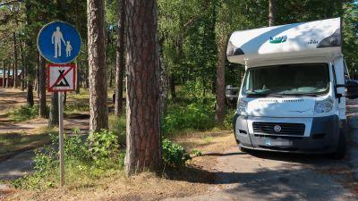 Bild av en husbil som är parkerad bredvid en skylt som förbjuder att slå läger.