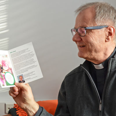 Roger Rönnberg kyrkoherde i Esbo svenska församling visar upp ett kort