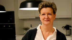 Camilla Klockars står inne i ett kök. Hon har vit skjorta och svart tröja på sig.