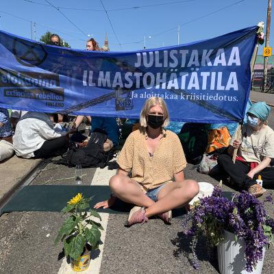 Aurora Blomberg protesterar för Elokapina framför en skylt.