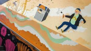 Seinämaalaus Martinlaakson juna-aseman sisäseinällä, mies jolla kädessä nakki, lentävä lokki, pesukone.
