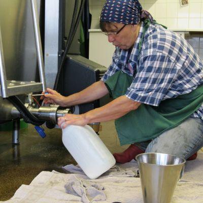 Marjaana Sjöblom fyller en kanister med mjölk.