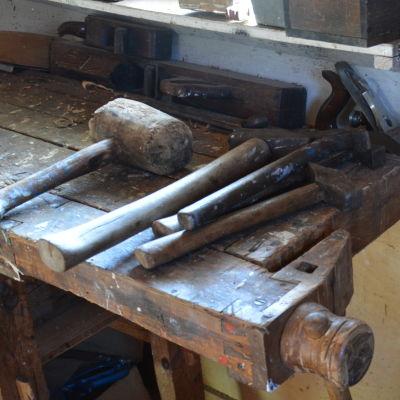 Gamla verktyg på en gammal hyvelbänk i trä.