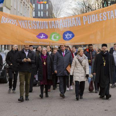 Eri uskontokuntiin kuuluvien yhteinen rauhankävely. Banderollissa teksti uskot yhteiskuntarauhan puolesta.