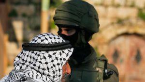 Palestinier och israelisk soldat i byn Salem öster om Nablus på Västbanken under en israelisk räd mot palestinier 18.3.2019