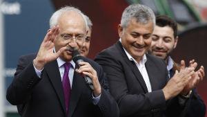 Oppositionsledaren Kemal Kilicdaroglu talar i en mikrofon och vinkar åt sina anhängare.