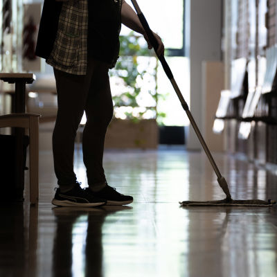 Siivooja moppaa lattiaa käytävällä.