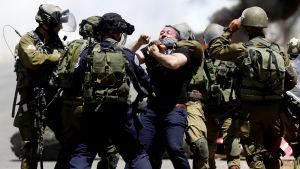 Israeliska soldater griper en palestinier som på fredagen demonstrerade för de hungerstrejkande fångarna i byn Beita, nära Nablus på Västbanken