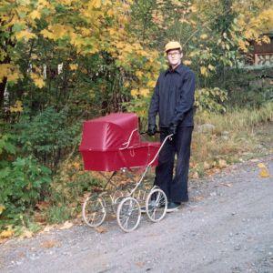 Mies ulkoilee puistossa lastenvaunujen kanssa.