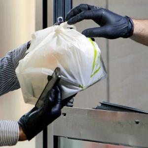 Ett matbud hämtar ett maketpaket från en restaurang i Bukarest mitt under coronaepidemin. Både matbudet och restaurangpersonalen bär skyddshandskar.