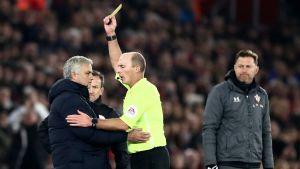 Jose Mourinho klappar om samtidigt som han får ett gult kort.