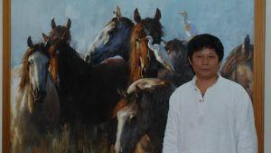 En person poserar framför en tavla med hästar.