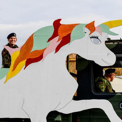 Yksisarvisen kuvalla varustettu armeijan ajoneuvo sotilaita kyydissään.