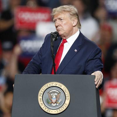 Donald Trump står bakom en officiell talarstol.