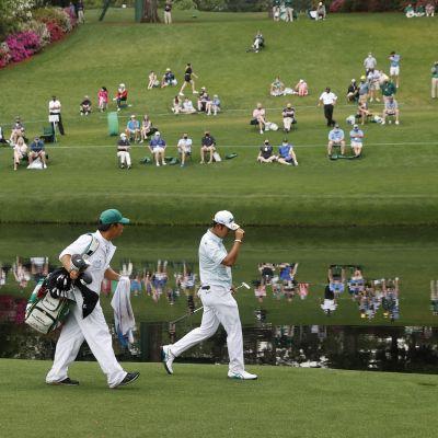 Hideki Matsuyama kävelee US Mastersissa lammen rannalla caddiensa kanssa. Lammen toisella puolella oleva yleisö heijastuu veden pinnasta.