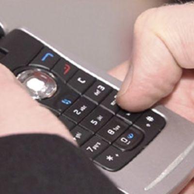 matkapuhelin kädessä