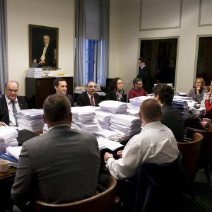 Grundlagsutskottet sitter samlat vid ett långt bord fullt med pappershögar.