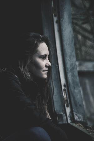 En ung kvinna tittar ut genom ett fönster och ser bekymrad ut.