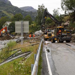 Två grävmaskiner röjer bort jord från en väg.