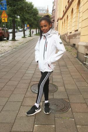 ung flicka med svart hår och brun hy står på en trottoar i vit rock och händerna i fickorna. I bakgrunden Åbo Konstmuseum