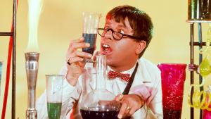 Hassunnäköinen mies katsoo laboratoriopurkkia.