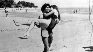 Mies kantaa hiekkarannalla naista sylissään