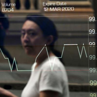 En kvinna passerade börsen i Sydney på tisdagen. Det ledande australiska börsindexet föll värst av alla asiatiska börser på måndagen, men återhämtade sig något på tisdagen.