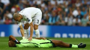 Vincent Kompany ligger och håller sig för pannan medan Pepe tröstar honom.