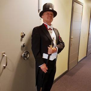Kunniatohtoriksi promovoitu kirjailija ja kuvataiteilija Hannu Väisänen frakissa ja hatussaan miekkä kädessä käytävässä seisomassa.