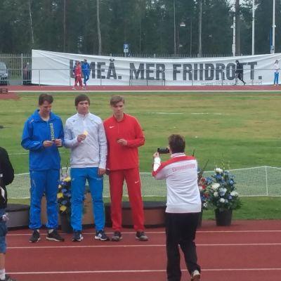 Tre idrottare står i bredd efter att ha fått sina medaljer.