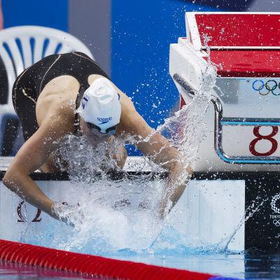 Fanny Teijonsalo står på knä bredvid startpallen och skvätter vatten i sitt ansikte.