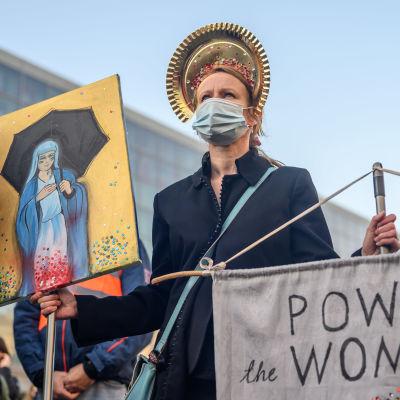 Nainen Neitsyt Marian kuvan ja valtaa naisille vaativan tekstin kanssa.