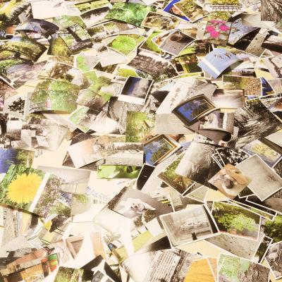 Massor av gamla fotografier med olika vardagliga motiv ligger ovanpå varandra i en hög.