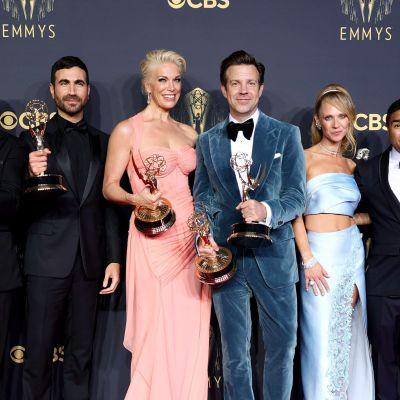 Ett gäng skådespelare poserar på röda mattan och håller i Emmystatyetter medan de ler.