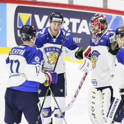 Finländska herrlandslagsspelare firar i klunga.