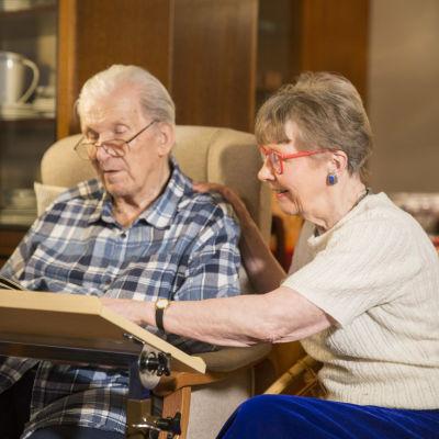 Mies ja nainen istuvat vierekkäin lukevat yhdessä miehelle kirjaa