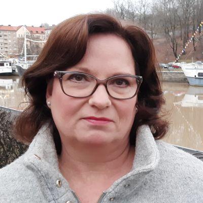 Mörkhårig kvinna vid åstranden i Åbo.