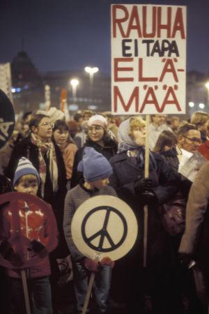 """Mielenosoittajia, lapsia ja naisia kokoontuneena Helsingin Hakaniementorilla. Kyltti, jossa iskulause """"Rauha ei tapa elämää"""" ja rauhanmerkki. Mielenosoitus rauhan puolesta."""